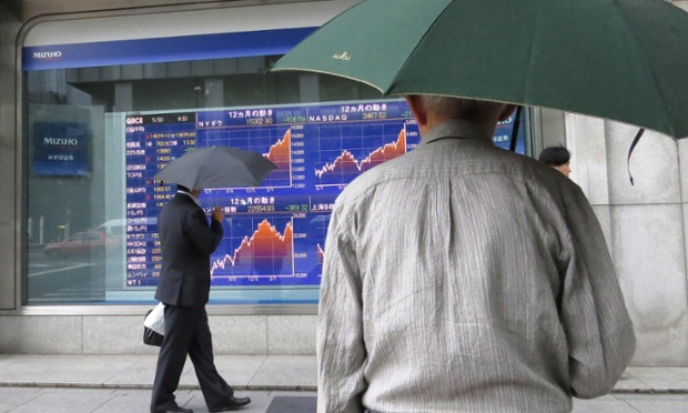Pedestrians watch a share price board in Tokyo on May 30, 2013.
