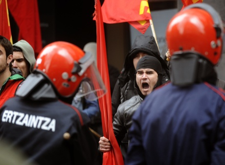 Members of union picket lines protest with Basque policemen at the entrance of a shopping mall during a regional strike called by the main Basque unions in the northern Spanish Basque city of Bilbao, on May 30, 2013.