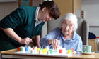 Elderly woman plays solitaire with a nurse