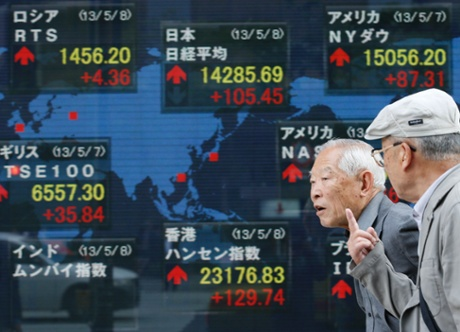Passers-by talk each other in front of an electronic stock board of a securities firm in Tokyo, Wednesday, April 8, 2013.
