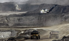 Mining trucks carry loads of oil-laden sand known as tar sand in Alberta, Canada