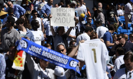 A fan of Real Madrid displays a placard reading