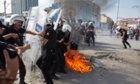 A petrol bomb explodes in front of riot policemen during clashes in Taksim square in Istanbul, Tuesday. Hundreds of police in riot gear forced through barricades in Istanbul's central Taksim Square early Tuesday, pushing many of the protesters who had occupied the square for more than a week into a nearby park.