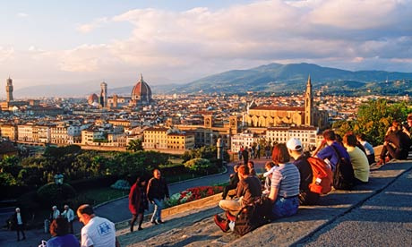 People resting on steps at Piazzale Michelangelo above Arno River and Florence near sunset