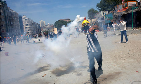 A protester throws a teargas cannister back at riot police in Taksim Square