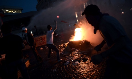 Protesters clash with riot police at Taksim square as darkness falls.