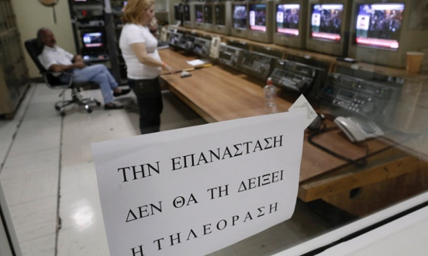 Employees work at a control room of the Greek state television ERT headquarters in Athens June 12, 2013. The sign reads: