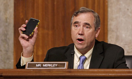 Senator Jeff Merkley waves his Verizon cellphone as he questions NSA director Keith Alexander on Wednesday. Photograph: Charles Dharapak/AP
