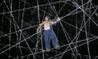 Actor Chris Ryan climbs a spiderweb in