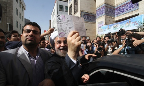 Hassan Rouhani shows his identity papers after casting his ballot in Tehran.
