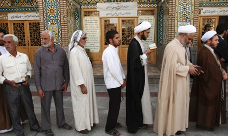 Men stand in line to vote during the Iranian presidential election at a mosque in Qom, 120 km (74.6 miles) south of Tehran.