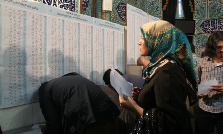 A woman looks at a board at a polling station in Tehran.
