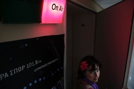 A woman enters a radio studio inside the state broadcaster ERT headquarters in Athens June 17, 2013.