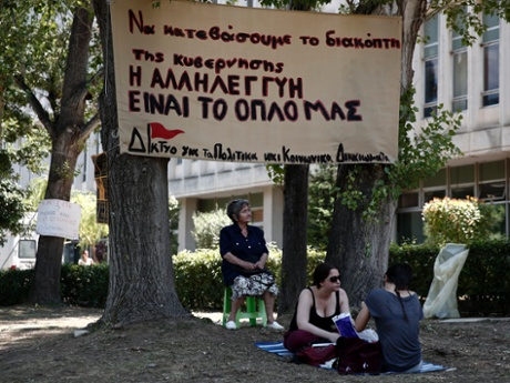 Supporters of the employees of state broadcaster ERT sit outside its headquarters in Athens June 17, 2013. The banner reads,
