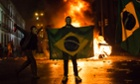 Brazil protest: A demonstrator holds a Brazilian flag in front of a burning barricade during a protest in Rio de Janeiro.
