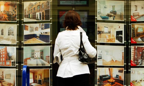 A woman looks at properties for sale in the window of an estate agent in central London