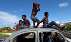Boys look at friends playing football from an abandoned Volkswagen Beetle in a shantytown of Olinda, Brazil, as the FIFA Confederations Cup football tournament is being held in the country.