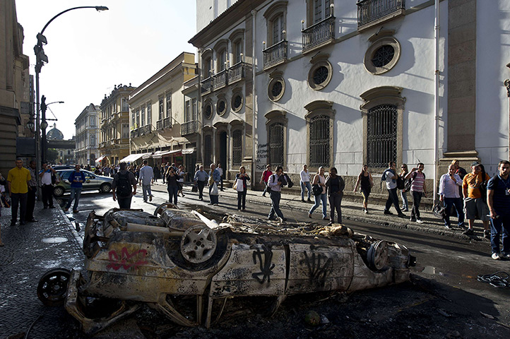 Brazil protests continue: People pass by a car burnt out car in downtown Rio de Janeiro,
