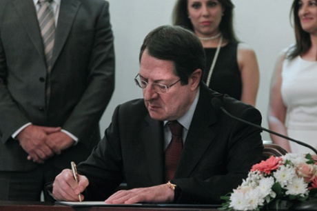 Cypriot President Nicos Anastasiades signing a document during the swearing-in ceremony for a new president and new judge of the Supreme Court, at the presidential palace in Nicosia on June 19, 2103.