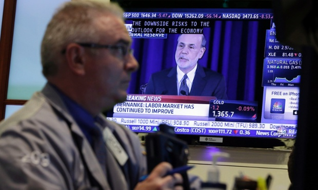 Fed Chairman Ben Bernanke is on a television screen as trader James Dresch works in a booth on the floor of the New York Stock Exchange Wednesday, June 19, 2013.