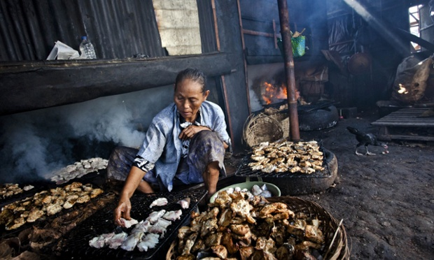 A Worker Cooks Fish In A Bandarharjo Smokehouse In