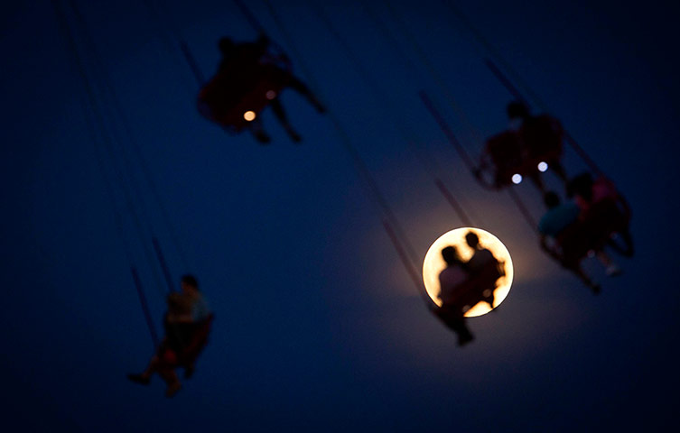super moon: People ride the Luna Park Swing Ride as the Super Moon