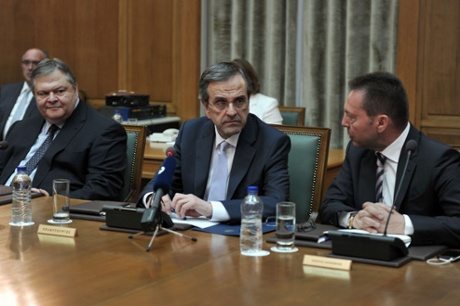 Greek Prime Minister Antonis Samaras (C)  talks with his Finance minister Yiannis Stournaras (R) while socialist Evangelos Venizelos (L) looks on, during the first cabinet meeting.