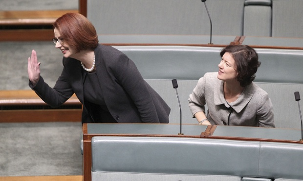 Taking a back seat: Former PM Julia Gillard waves as she sits next to Kirsten Livermore in the House of Representatives.
