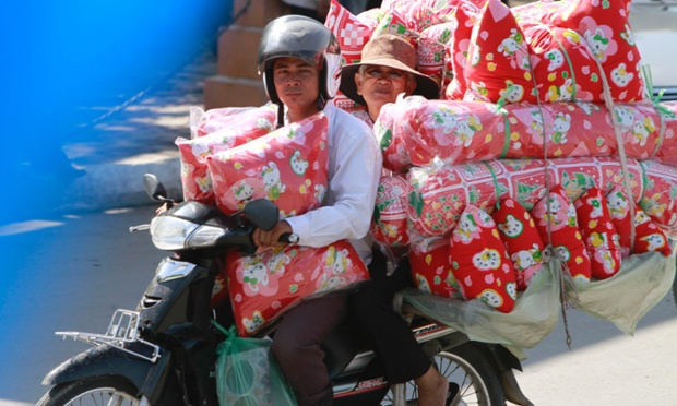Cambodian people ride a motorcycle overloaded with cushions in Phnom Penh