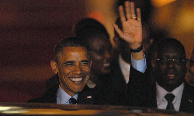 President Barack Obama waves to onlookers as he arrives in Dakar, Senegal on the first stop of a three-country tour.