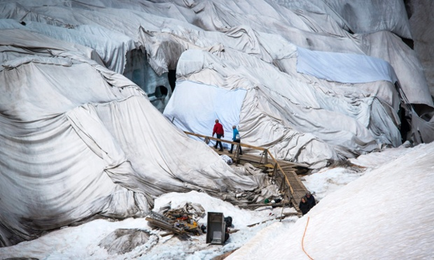 People entering the grotto of the Rhone glacier in the central Alps of Switzerland. The glacier is protected by blankets at this time of the year to keep ice melting to a minimum.
