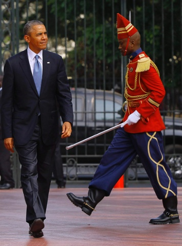 President Barack Obama is followed by a member of the honour guard at the Presidential Palace.