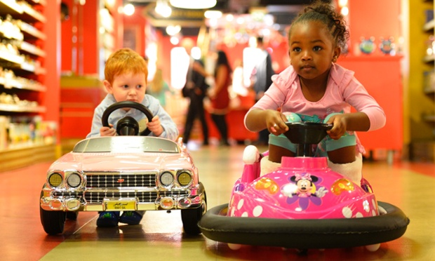 Tristan Robertson Jeyes, 2, drives a £250 pounds pink Cadillac next to Jayla Silva, 3, on a £160 pounds mini dodgem in Hamleys toy store.