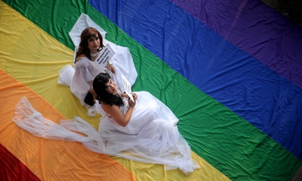 Supporters of lesbian, gay, bisexual, and transgender groups dressed in weddings gowns sit on a huge rainbow banner at the University of the Philippines in Manila as they celebrate Pride Month.