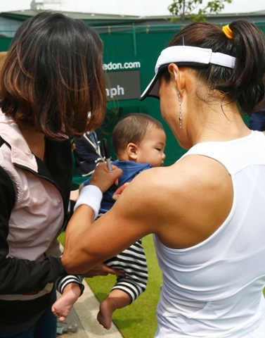 Backhand: Kimiko Date-Krumm of Japan signs her autograph on a child's t-shirt after defeating Alexandra Cadantu of Romania.