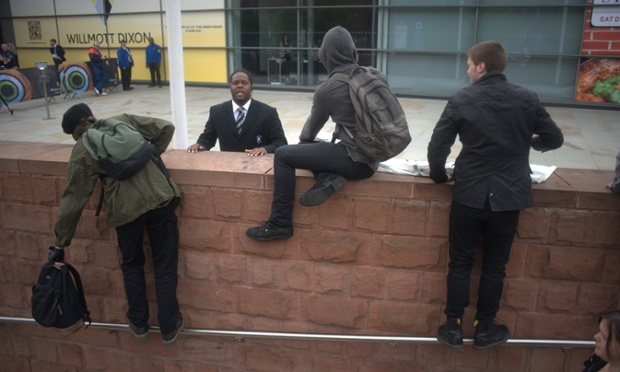 Protesters trying to climb over a wall in Manchester to get round the cordon created to stop protesters demonstrating outside the Chartered Institute of Housing during the visit of Lord Freud, a minister of state in the Department of Work and Pensions.