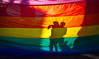 couple behind a rainbow flag