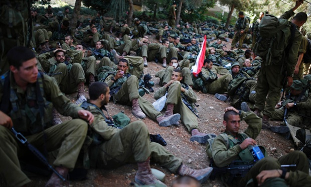 Israeli paratroopers rest during a march near Jerusalem, marking the completion of their advanced training, at the end of which they receive their red paratrooper's beret.