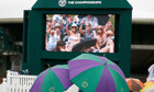 Spectators sit under umbrellas on Murray Mound at the Wimbledon Tennis Championships, in London