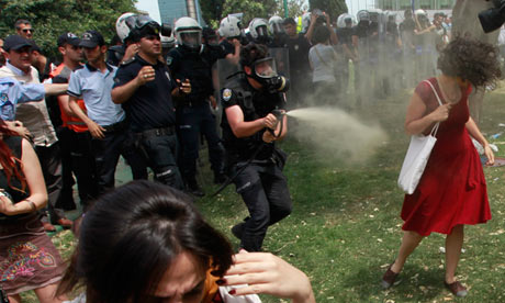 Turkish riot policeman uses tear gas against woman