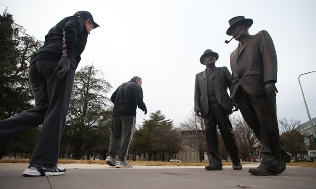 Walkers pass the statues of Labor wartime leaders Ben Chifley and John Curtin on a brisk Canberra morning.