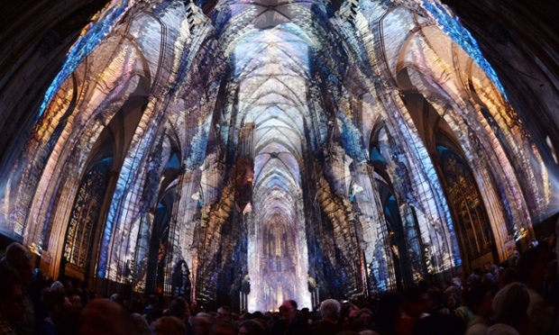 People watch a light installation inside the Cologne cathedral in Germany