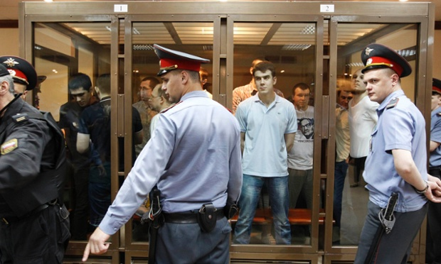 Defendants facing trial over clashes with the police during an anti-Putin protest last year, stand inside a glass-walled cage before a court hearing in Moscow, during a case Kremlin critics liken to Soviet-era show trials of dissidents.