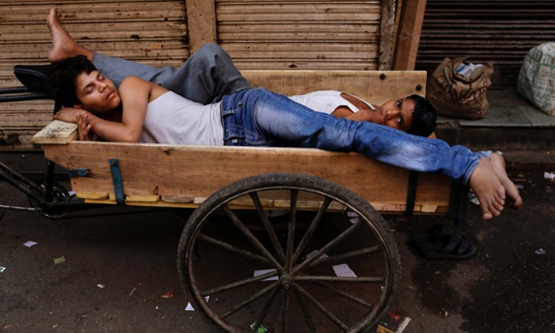 Young Indian labourers rest on a delivery bicycle in New Delhi.