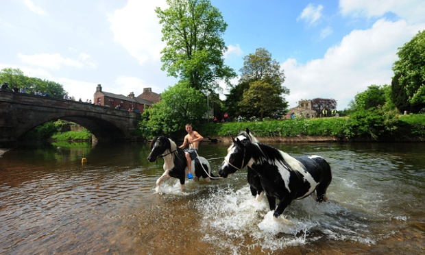 A man takes horses into the River Eden for a wash at the Appleby Horse Fair in Cumbria.