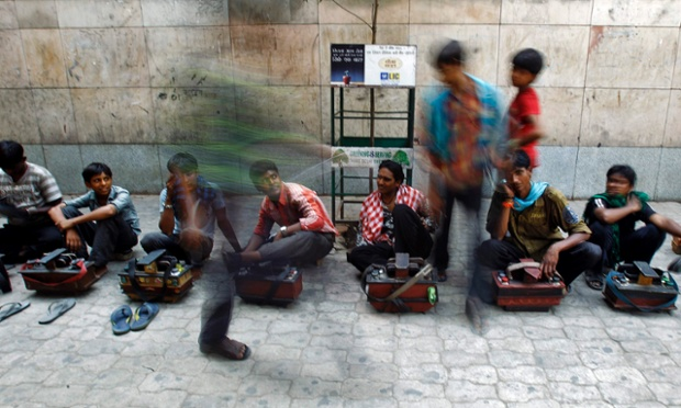 A commuter walks past cobblers waiting for customers outside a metro station in New Delhi
