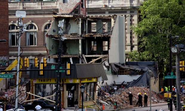 Firefighters view the aftermath of a building collapse in Philadelphia. On Wednesday, the building, under demolition, collapsed onto a neighboring thrift store, killing six people and injuring 14, including one who was pulled from the debris nearly 13 hours later.