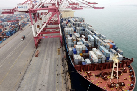 In this photo taken Monday July 8, 2013, a ship is docked at a container port in Qingdao in eastern China's Shandong province.