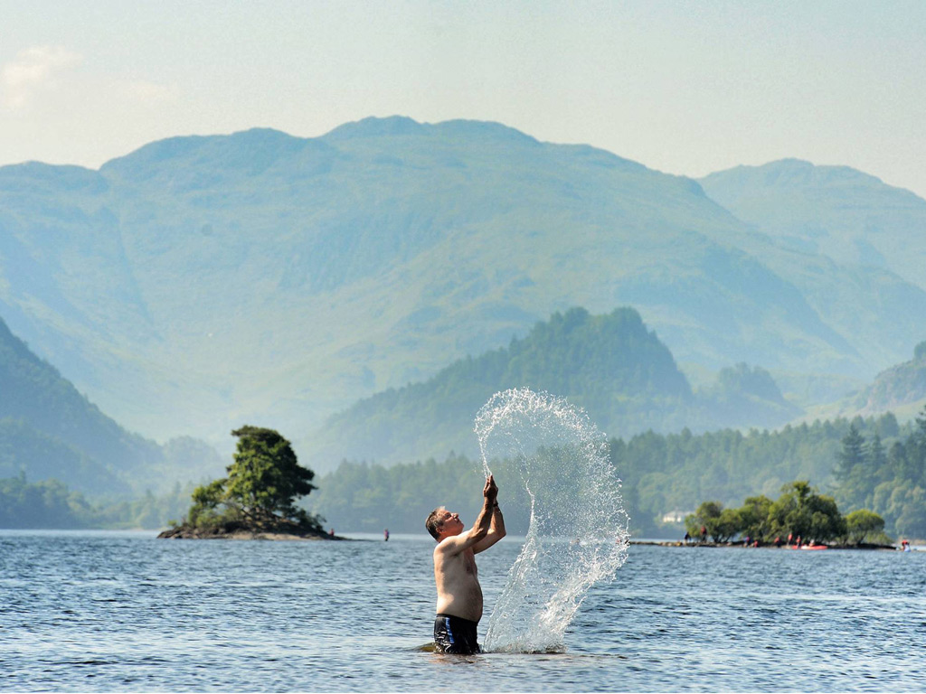 A visitor to Derwentwater in the Lake District takes a break from the searing heat with a cooling di