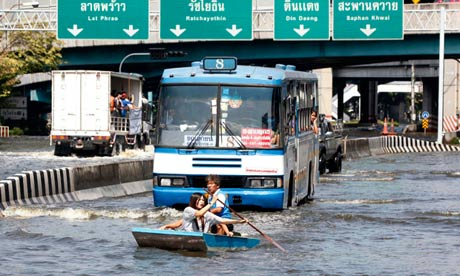 Residents row a boat in front of a bus along a flooded street in Bangkok